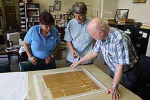 Examining the original map that Robert E Lee used during the Seven Days Campaign in the American Civil war in the archives department of the Museum of the Confederacy in Richmond Virgnia, Theresa Roane, Travel Extra editor Eoghan Corry and Sam Craghead.
