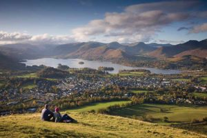 A couple sitting on the fell at Latrigg overlooking Keswick in the Lake District by Derwentwater lake in the distance.